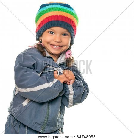 Funny mixed race little girl wearing a colorful beanie hat and a jacket isolated on white