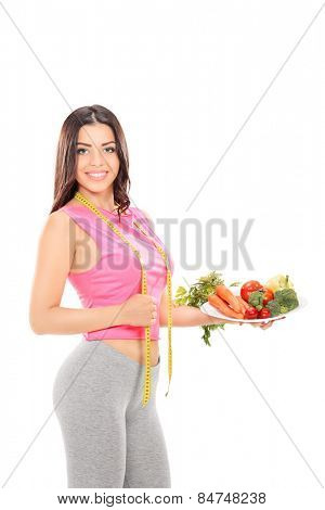 Vertical shot of a woman holding a plate full of vegetables isolated on white background