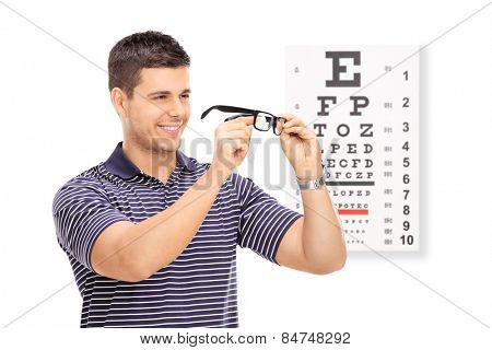 Man wiping his glasses in front of an eye chart isolated on white background