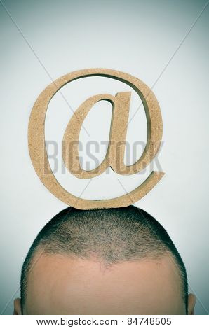 closeup of a young man with an at sign in his head