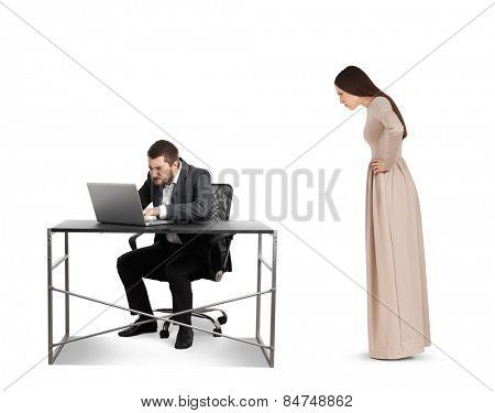 angry woman staring at concentrated businessman with laptop. isolated on white background