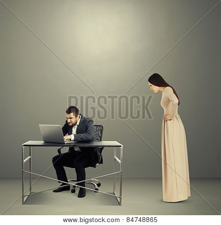 concentrated man looking at laptop, angry woman staring at man. photo in dark room