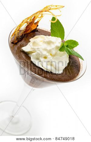 Homemade chocolate mousse in a martini glass with cream, a sprig of mint and a caramelised sugar decoration