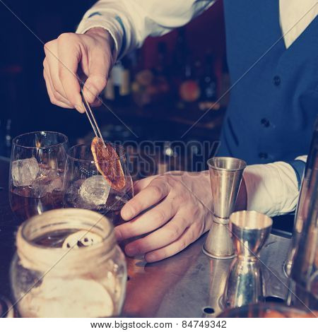 Barman works at bar counter, blue toned image
