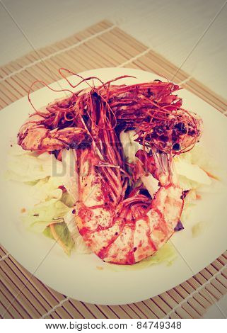 Seared Jumbo prawns with lettuce on restaurant table, toned image