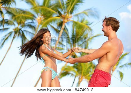 Beach couple fun on vacation dancing playful. Happy young lovers enjoying summer vacation holiday on beach. Beautiful interracial couple in love. Asian woman, Caucasian man on Hawaii.