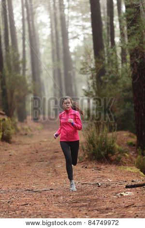 Running woman in forest woods training and exercising for trail run marathon endurance race. Fitness healthy lifestyle concept with female athlete trail runner.