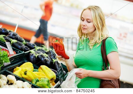 Shopping. Woman choosing bio food fruit pepper paprica in vegetable store or supermarket