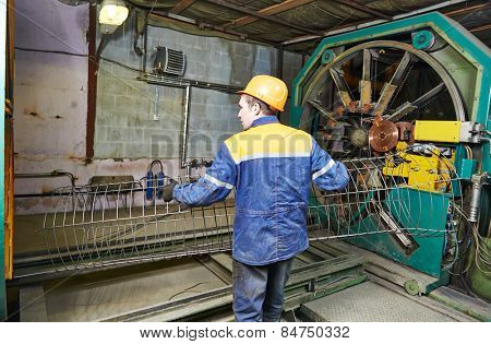 industrial worker making metal reinforcement carcass for concrete tube pipe