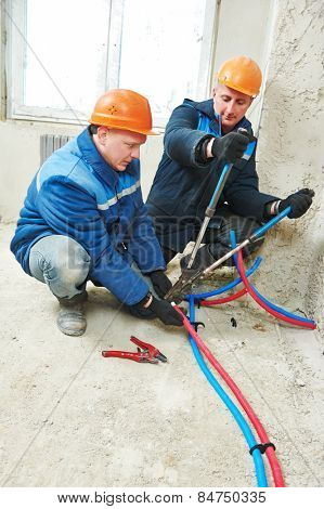 two repairman engineer installing house floor heating system at interior construction site