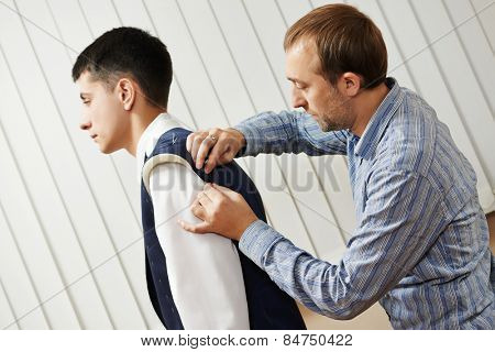 male tailor designer make marks on a jacket during bespoke suit fitting
