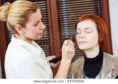 Makeup technique. specialist works with mascara eyelashes of redheaded woman in beauty salon