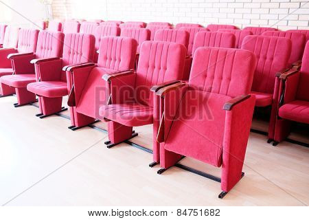 Large red recliners stand rows in an empty hall
