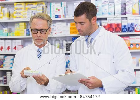 Team of pharmacists looking at medicine box at the hospital pharmacy