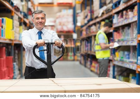 Manager pulling trolley with boxes in front of his employee in warehouse
