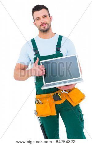 Smiling construction worker holding laptop on white backboard