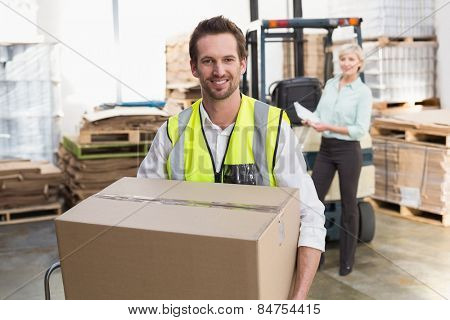 Smiling warehouse worker carrying box in warehouse