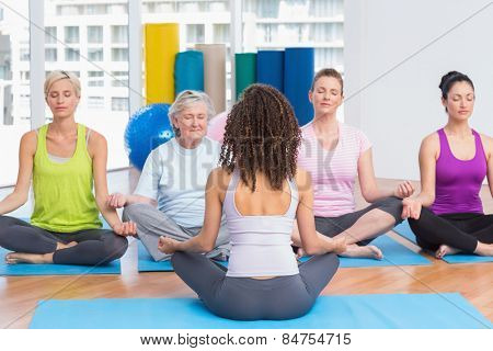 Group of people practicing lotus position in yoga class