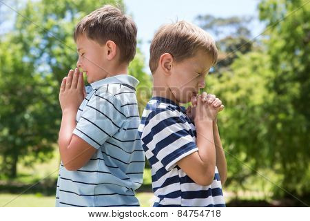Little boys praying in the park on a sunny day