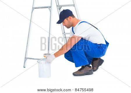 Full length side view of handyman with paint can on white background