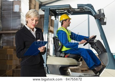 Manager writing on clipboard in front of her colleague in a large warehouse