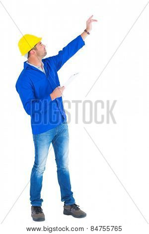 Full length of supervisor with hand raised holding clipboard on white background