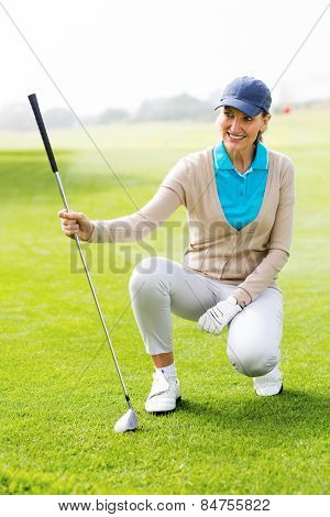 Female golfer kneeing on the putting green on a sunny day at the golf course