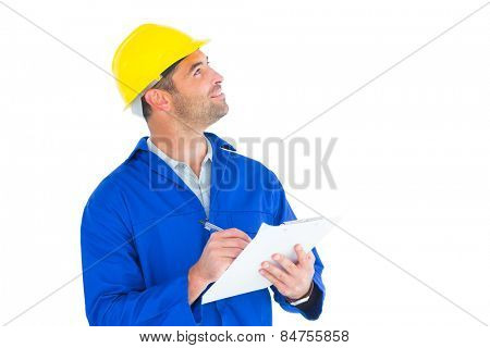 Male supervisor looking up while writing on clipboard on white background