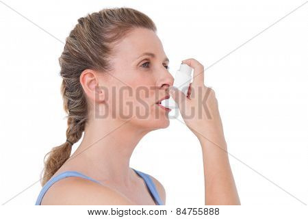 Woman using inhaler for asthma on white background