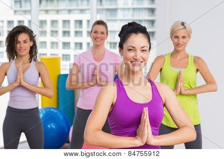 Portrait of happy women with hands joined exercising at gym