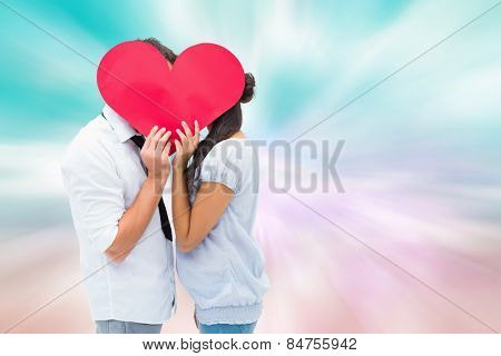 Couple covering their kiss with a heart against digitally generated pink and blue girly design