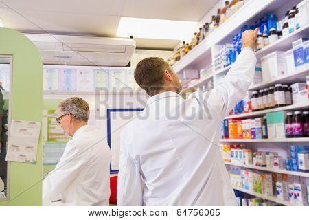 Pharmacist in lab coat taking jar from shelf in the pharmacy