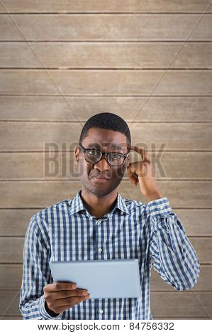 Young businessman thinking and holding tablet against wooden planks