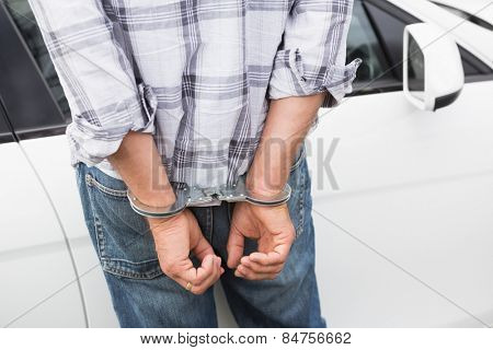 Man in handcuffs standing by his car