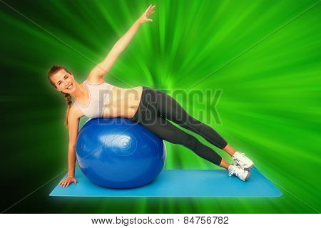Portrait of a fit woman stretching on fitness ball against abstract background