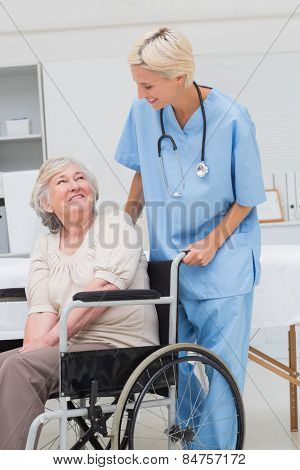 Happy female nurse looking at senior patient sitting on wheelchair in clinic