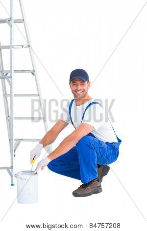 Full length portrait of smiling handyman in overalls opening paint can on white background