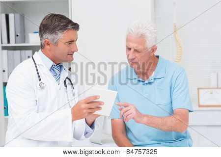 Male doctor explaining prescription to senior patient in clinic