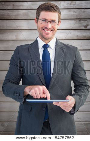 Businessman using his tablet pc against wooden planks
