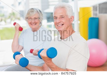 Portrait of happy senior couple lifting dumbbells in gym