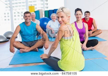 Portrait of female instructor with class practicing yoga in fitness studio