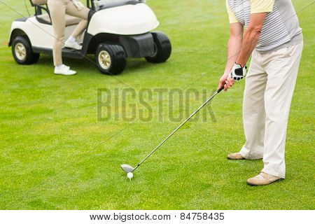 Golfer about to tee off with partner behind him on a foggy day at the golf course