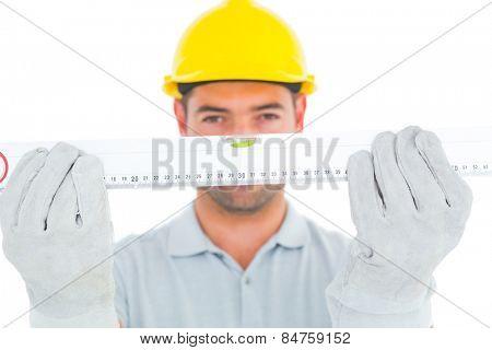 Portrait of handyman holding spirit level on white background
