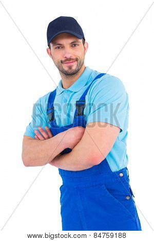 Smiling male handyman in coveralls standing arms crossed over white background