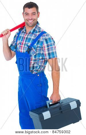 Portrait of happy repairman with toolbox and monkey wrench on white background