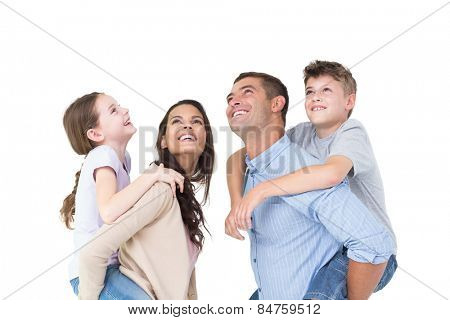 Happy parents giving piggyback ride to children while looking up over white background