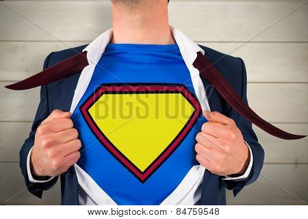 Businessman opening shirt in superhero style against bleached wooden planks background