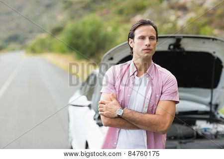 Man waiting assistance after a car breakdown at the side of the road