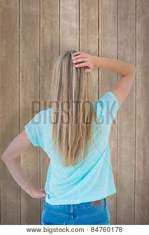 Rear view of a blonde posing with hand on hip against wooden surface with planks