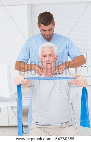 Male physiotherapist assisting senior man in exercising with resistance band at clinic